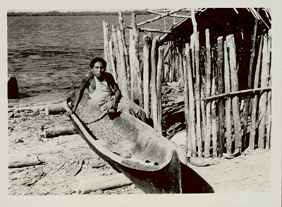 Cuna Man with Dugout Canoe Outside Pole Structure; Thatch Roof And Pole House Near Water APR 1939