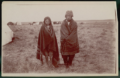 Young Woman and Man Wearing Blanket Robes Outside Toldo (Canvas and Pole Tent); Toldos in Distance JAN 1898