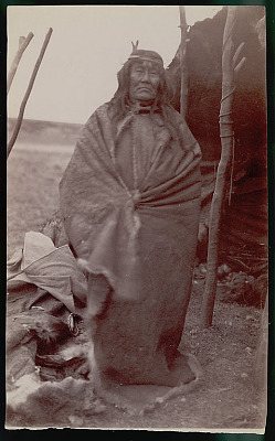 Old Man Wearing Guanaco Robe and Headband Outside Toldo (Skin and Pole Tent) FEB 1898