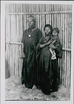 Amahuaca? Man, Woman, and Young Girl Wearing Face Paint and in Costume Outside Bamboo House JUL 1910