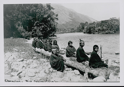 Group of Amahuaca Men, Boys, and Girl Wearing Face Paint and in Costume at River's Edge; Mountains in Distance JUL 1910