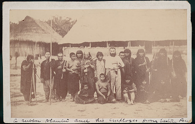 Man, Non-Native Rubber Plantation Owner, and Group, Employees In Costume, Some with Nose Rings, Bows, Arrows, and Guns, Outside Pole Houses with Thatch Roofs 1893