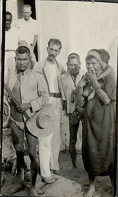 Three Non-Native Men and Two Men with Woman in Costume, Holding Young Boy and Carrying Burden Baskets with Tumpline, Outside Stucco Building 1924
