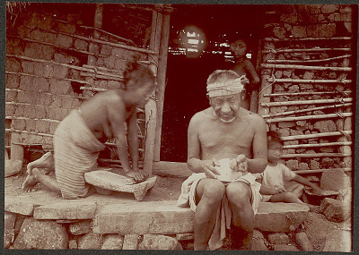 Woman Milling with Mano and Metate, Old Man Carving Gourd Bowl, and Young Boy Cooking? with Comal (Griddle) Over Hearth; All in Costume Outside Pole and Adobe Brick House; Boy in Doorway 1902