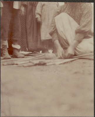Woman in Costume, Weaving Reed Mat and Using Rock Weight; Group Watching 1902