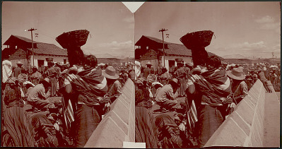 Group in Costume at Outdoor Market; Woman Carrying Basket On Head and Infant on Back, Near Adobe Brick, Stucco Building With Tile Roof 1909