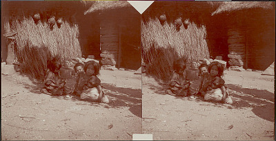 Two Young Girls and Young Boy in Costume Outside Brush House and Adobe Brick House with Thatch Roof; Gourd Jugs Hanging from House Wall 1909