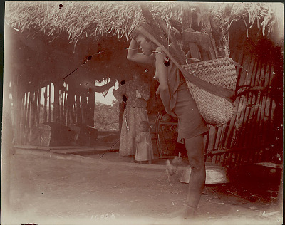 Young Woman in Costume, Carrying Burden Basket Full of Wood And Ax with Tumpline Outside Bamboo and Thatch House; Woman And Young Girl Inside House 1901