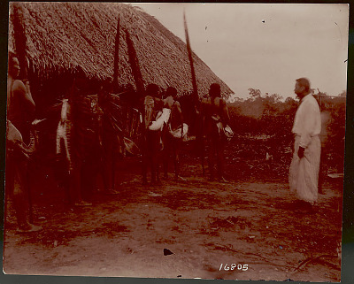 Group of Men Carrying Large Fish and Nets and with Non-Native Man (W a Cook) Outside Pole and Thatch House 1901