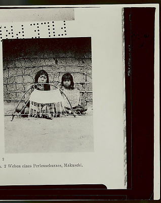 Photo of Woman in Costume, Weaving Beaded Skirt on Hand Loom; Young Girl with Beaded Skirt Beside Her, Outside Mud and Pole House 1923