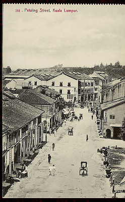 View of Commericial District Showing Storefronts and Group In Street with Jinrikshas n.d