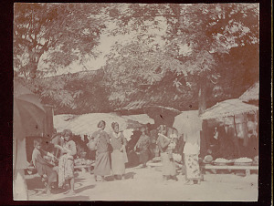 images for Pasar (Market Place): Group in Costume Near Woven Mat Umbrellas and Fruit Stalls of Colonnaded Stucco Building with Tile Roof 1896-thumbnail 1