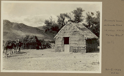 Wattle and Daub House with Straw Roof and Brush Structure; Man with Team of Donkeys and Dog Nearby; Mountains in Distance 30 JAN 1922