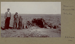 Non-Native Man (Possibly Named Stuwman?) with Rifle, Aged Native Man with Bow, and Aged Native Woman Outside Brush Structure In Desert; Metal Cookware Nearby 1899
