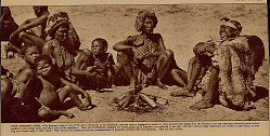 Abraham, 106 Years Old, Bushman Patriarch of Southern Kalahari, In Costume and Holding Switch and with Two Women in Costume And Children, One with Face Paint, Around Campfire SEP 1936