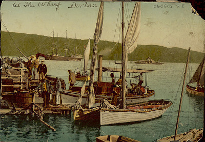 View of Wharf Showing Sailboats and Passenger Boat at Dock With Group of Men, Boats, and Woman; Three-Masted Sailing Ship And Other Boats in Distance n.d