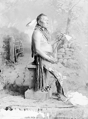 Chief White Horse in Native Dress with Bear Claw Necklace, Ornaments and Holding Pipe-tomahawk n.d