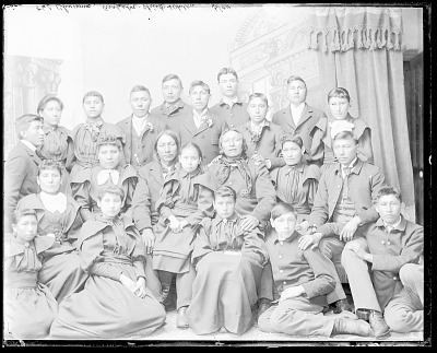 Portrait of Two Visiting Cheyenne and Arapaho Chiefs, One Wearing Military Jacket, with Group of Students in School Uniform MAR 1894