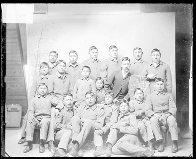 Portrait of Group of Boys in Uniform, and Non-Native Man JAN 1890