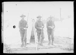 Three Non-Native Soldiers in Uniform and with Guns, Outside Tent; Other Tents Nearby n.d