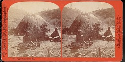 """""""Digger"""" camp scene with two Indians sitting outside a grass wigwam"""