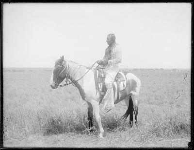 Cheyenne Indian man on horseback. Oklahoma. Leader of a Sun Dance Society in Ceremonial Attire 1903
