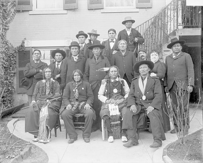 Fourteen Delegates in Partial or Full Native Dress, Two with Peace Medals, Outside Ben Beveridge's Hotel; Two Non-native Men with Them JAN 1899