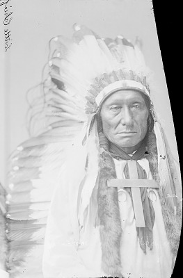 Portrait (Front) of Kuc-Kun-Ni-Wi or Hach-Ivi (Little Chief) or Magpie Eagle Feathers, in Partial Native Dress with Headdress and Cross Necklace 1879