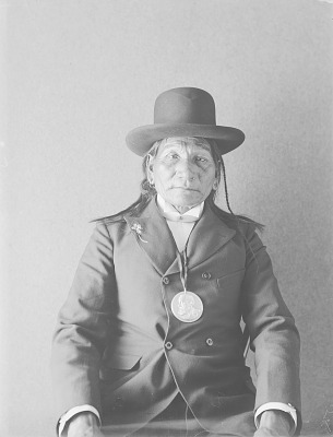 Portrait (Front) of Kuc-Kun-Ni-Wi or Hach-Ivi (Little Chief) ? or Magpie Eagle Feathers? with Benjamin Harrison Peace Medal and with Ornaments MAR 1895