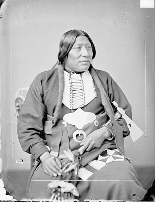 Portrait (Front) of Min-Nin-Ne-Wah (Whirlwind) in Partial Native Dress with Breastplate and Gorget? and Holding Pipe-tomahawk 1877