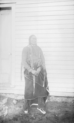 Woir-Oqtuimanists (Man on a Cloud) in Native Dress; Wood Building Nearby 1892