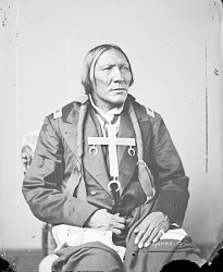 Portrait (Front) of Hah-Ket-Home-Mah (Little Robe) in Partial Native Dress and Military Coat and with Cross Necklace 1871