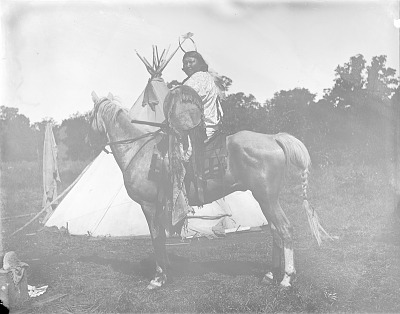 Tsen-Tainte (White Horse) in Partial Native Dress and Holding Shield and Rifle, On Horseback Near Tipi 1892
