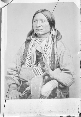 Portrait of Chief Tene-Angopte (Kicking Bird) in Partial Native Dress, Wearing Blanket with Hairpipe Breastplate and Holding Bow and Arrows in Fur Quiver 1868