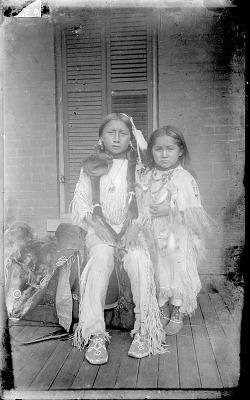 Two Children of Ongotoya (Solitary Traveler) Bow, Jr, in Native Dress near Brick Building 1892