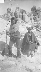 Masai-Uniuwa in War Costume with Gun and Maiden in Native Dress near Rock Formations n.d