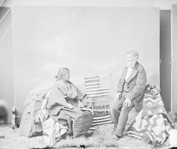 Portrait of Juanita in Native Dress; Blankets, Weaving Implements and Governor Arny Nearby 1874