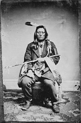 Portrait (Front) of Zitka Sapa Maza or Zin-Tka-Sha-Pa-Ma-Za or Pte-Yah-Pa-Ma-Sa (Iron Black Bird) in Native Dress with Ornaments and Holding Pipe and Bag 1867