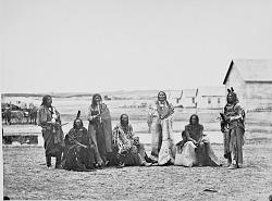 Group of Seven Men Near Wood Frame Buildings 1868