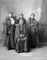 Portrait (Front) of Group of Women from Fort Peck (L-R): Gertie Wets It in Non-Native Dress; Unidentified Young Woman; Girl Who Stays at Home; and Mrs Wets It in Partial Native Dress 1898