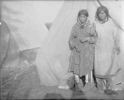 [Two Eskimo women in front of a canvas tent]