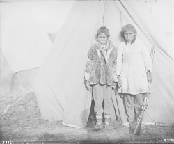 [Two Eskimo men in front of a canvas tent]
