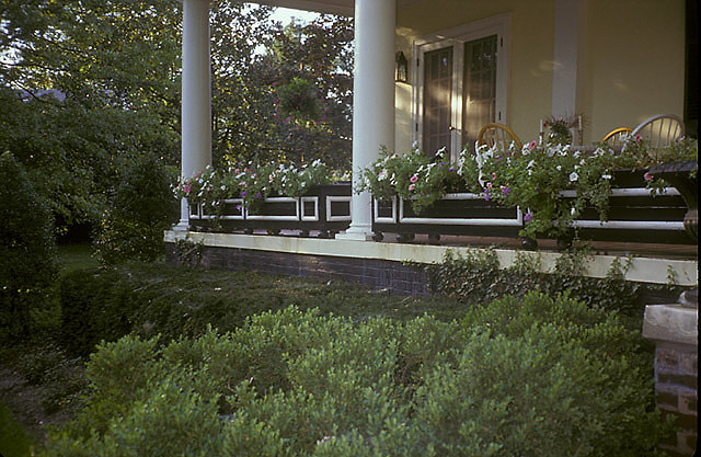 [Leachman Garden]: front porch with petunias in long planters.