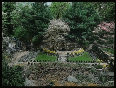 [Ferncote] [slide]: sunken garden with wall fountain and boxwood edging; lattice fence with patio furniture to the left