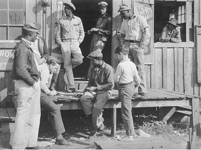 Migrants playing checkers (with bottle caps), on a juke joint porch after a