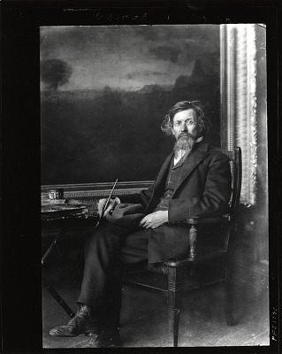 George Inness seated in his studio in front of painting