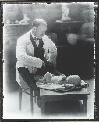 Paul Manship in his studio seated beside