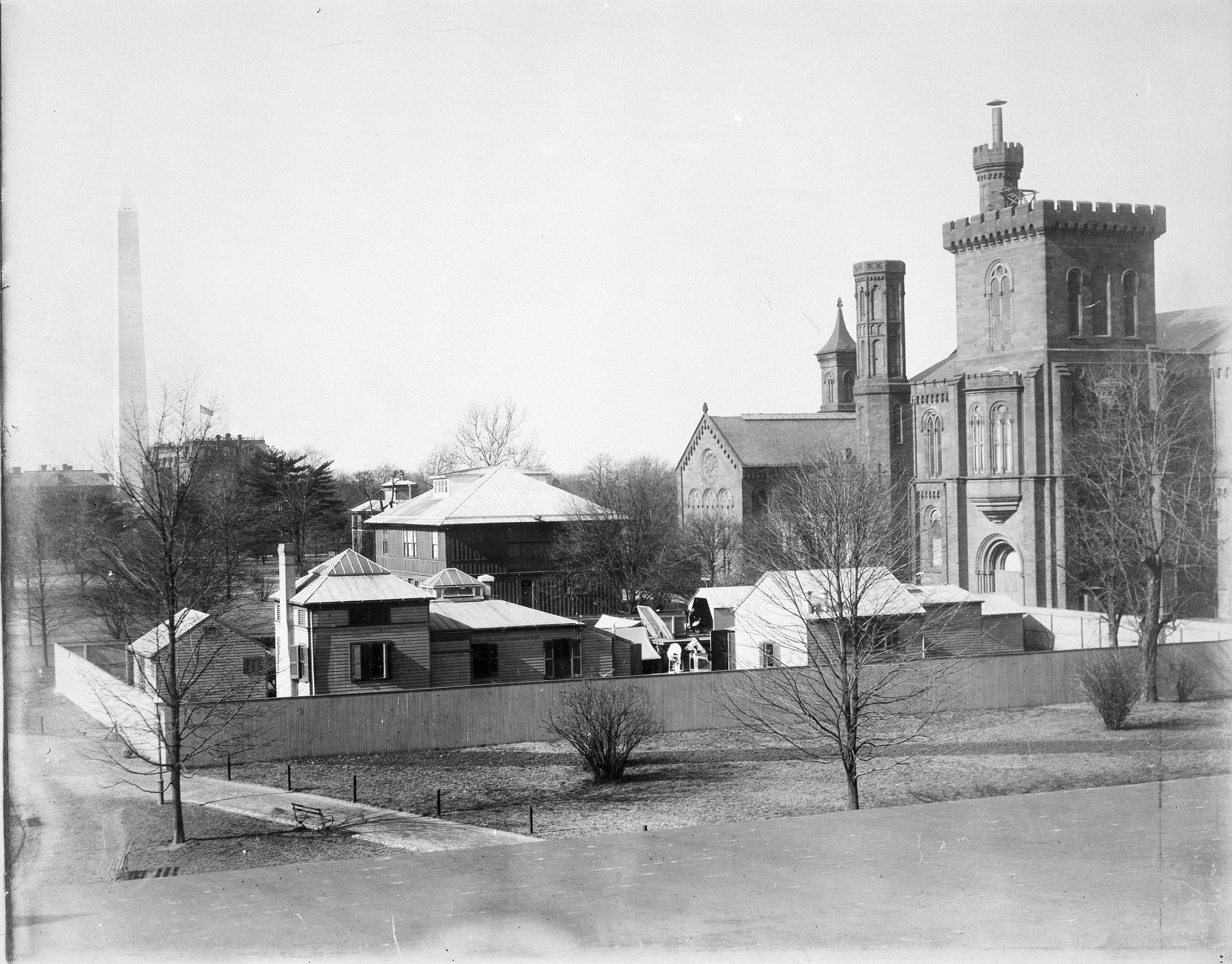 The Smithsonian Astrophysical Observatory located in the South Yard behind the south facade of the Smithsonian Institution Building. The Astrophysical Observatory is enclosed by a wooden fence. The Annex, also called the South Shed, is behind the Observatory. The Laboratory of Natural History, the old Agriculture Building, and the Washington Monument are visible in the background