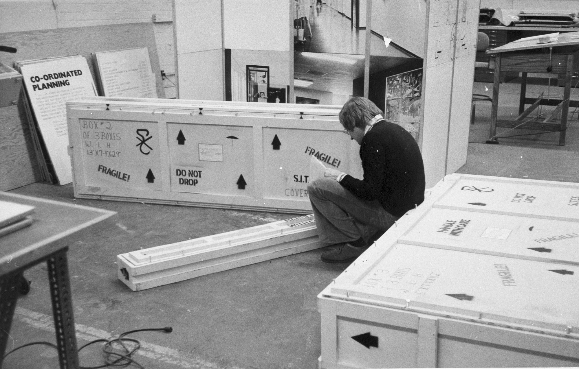 Dennis Gould Checking Crates, by Unknown, c. 1974, Smithsonian Archives - History Div, 94-2468.
