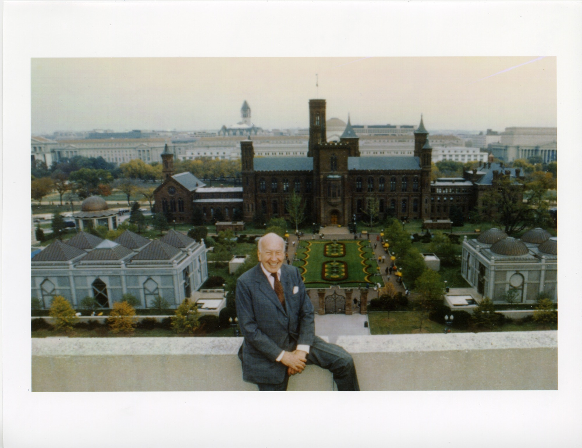 Smithsonian Secretary S. Dillon Ripley sitting on roof of building  across from South Yard. Aerial view of Quadrangle shows Smithsonian  Institution Building (SIB) or Castle, Enid A. Haupt Garden, National  Museum of African Art (NMAfA) and Arthur M. Sackler Gallery (AMSG). The  National Mall and National Museum of Natural History can be seen behind  the Castle in the distance.